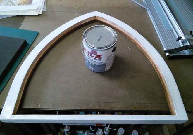 An arched window, primed & reamed out to fit the new glass.