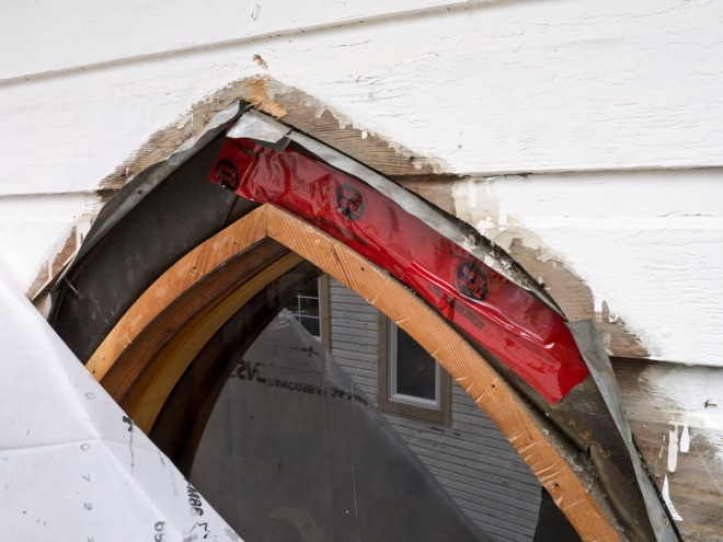 Metal flashing over arched window frame.