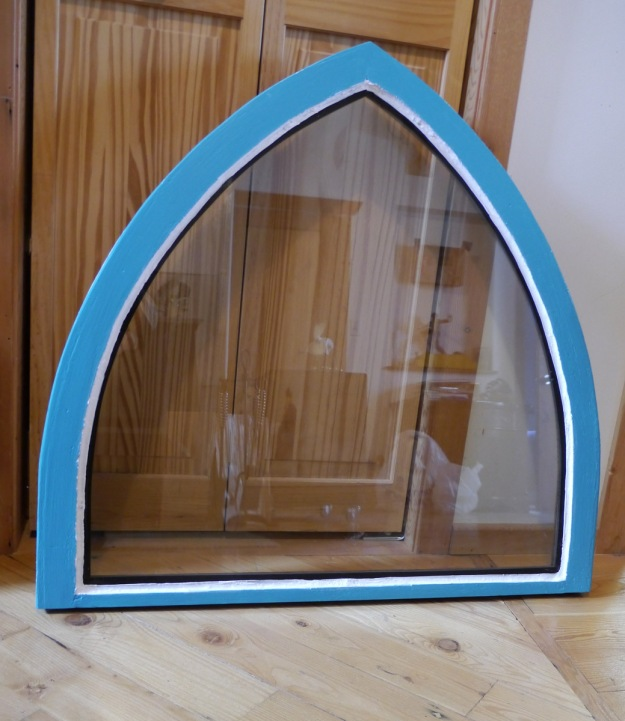 A rebuilt arched window, freshly painted, with new glass.